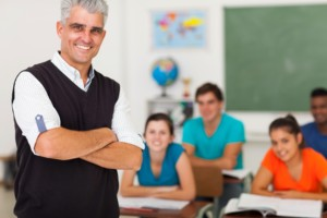 Smiling middle aged high school teacher with arms folded standing in front of the class
